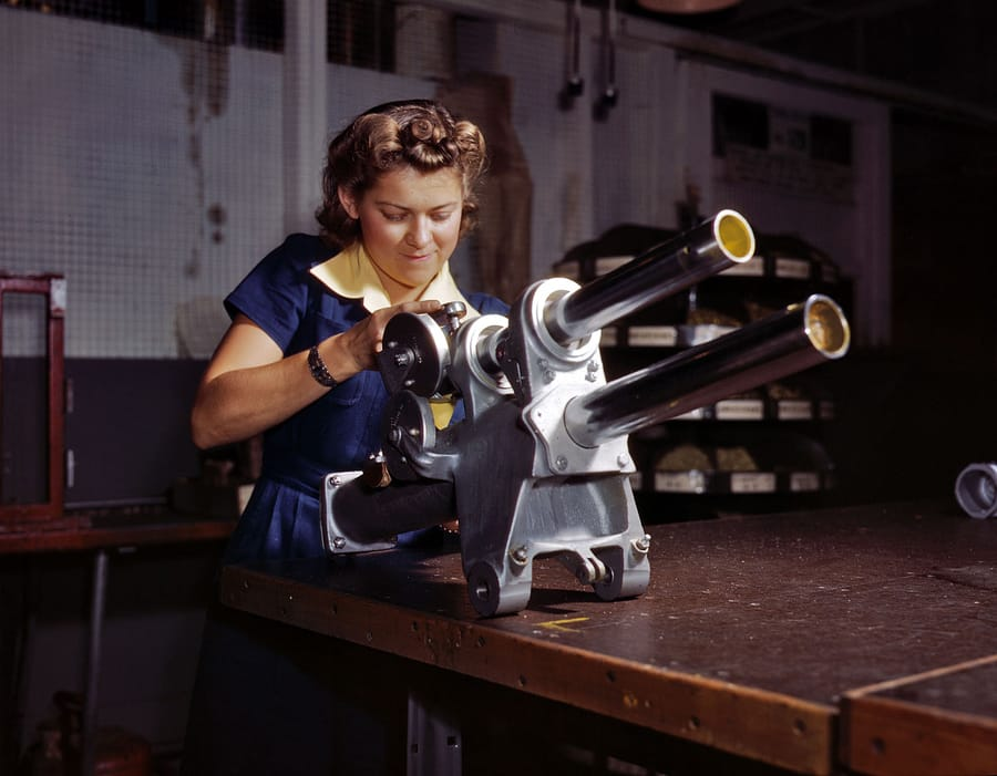 "October 1942. Inglewood, California. ""Young woman employee of North American Aviation working over the landing gear mechanism of a P-51 fighter plane."